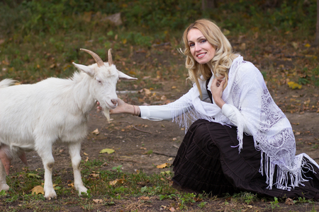 Tender woman stroking white goats on a green glade 스톡 콘텐츠