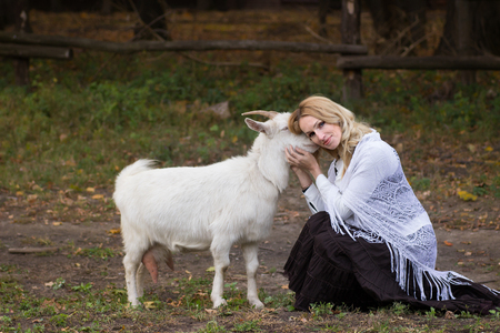 Blonde woman stroking white goats on a green glade