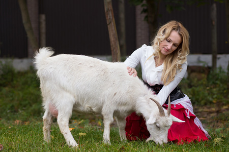 Positive woman stroking white goats on a green glade