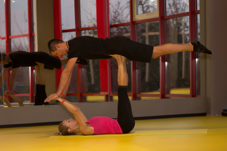 Couple practicing bird pose during yoga class in modern fitness center. Acro yoga