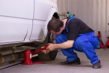 Mechanic uses jackscrew in the auto service