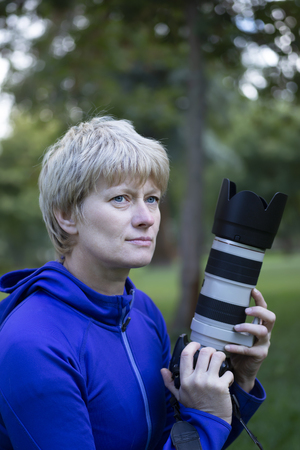 Professional photographer. Portrait of confident adult woman holding camera in hands in the park