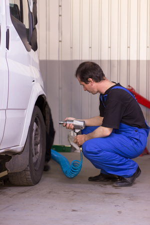 Mechanic is pumping up wheels in a car service station Stockfoto
