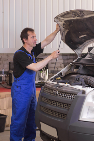 Technician working in the auto service and repairing a car