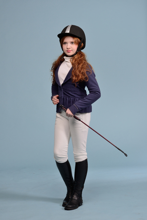 redhead girl with freckles in riding clothes and helmet on a light background, the concept of a jockey