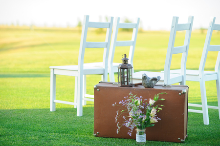 white chairs, suitcase, flowers, lawn Stock fotó