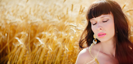 A field of wheat. Beautiful woman eyes closed, sensual lips. Ears of Golden wheat closeup. The concept of a rich harvest. Copy space for your text. A wide banner. Summer sale