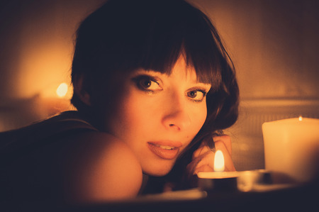 beautiful romantic woman in a bathtub with candles, warm and cozy color toning