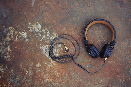 brown classic headphones with a wire on a rusty background. 版權商用圖片