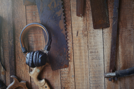 wireless headphones brown on the background of joiners tools, craft and leisure.