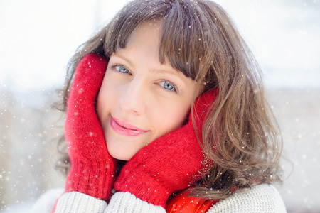 Christmas sale. Beautiful surprised woman in red mitts and white sweater winter background with snow, emotions. Funny laughter woman portrait. New year sales Stock Photo