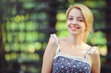 A healthy woman. Beauty Summer model girl with bright flowers happy forest. style leisure. A beautiful white lady. A nice face with a smile and a mystery. place for banner and advertisement.