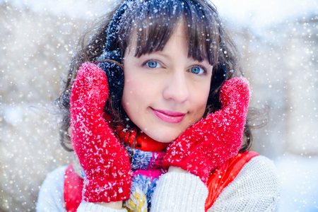 Outdoor bright photo of young beautiful happy smiling girl in the mitts, outside. dressed in stylish bright winter clothes, the snow falls. Pull. Christmas, New Year, concept. Magical snowfall. Stock Photo