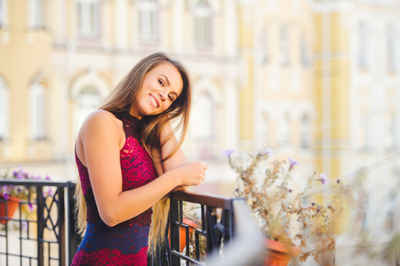 Beauty Glamor Woman smiling looking with interest. He laughs. Long hair. Fashionable lady with a beautiful hairdo, makeup. on the background of the city. fashionable dress.
