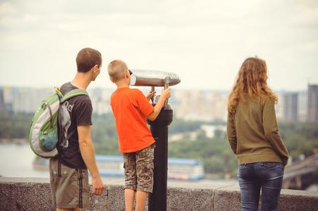 tourist looks at the city through binoculars. Stock Photo