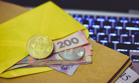 bitcoin network: Bitcoin gold coin lies in an envelope with money on the background of the computer and the rising graphics. The concept of virtual crypto currency.