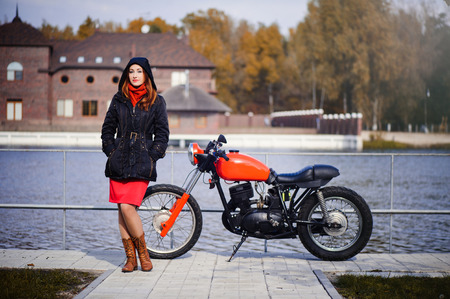 young pretty woman in a hood in the cold season against a red motorcycle and yellow forest, red hair and a scarf around her neck.