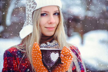 Valentine's day, woman with winter cup with heart close up on snowy background. Woman holding hands in teal gloves, holding in a cozy mug with hot. The concept of winter and love