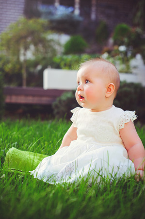 half-year-old child sitting on the grass in the yard, dressed in a white dress rejoices, 6 months. Concept education of children, childrens goods. Stock Photo