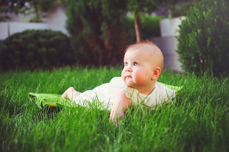 half-year-old child crawls on the grass in the yard, dressed in a white dress rejoices, 6 months. Concept education of children, childrens goods. Stock Photo