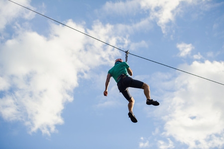 a man descends on a rope, a sport in an extreme park, A man walking along a zip line,