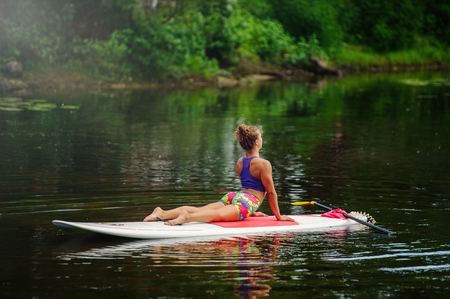 Young athletic woman doing fitness on a board with an oar on a lake. Stock Photo