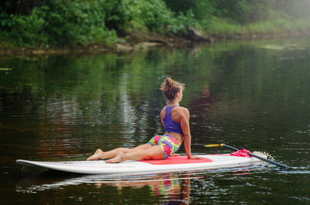 Young athletic woman doing fitness on a board with an oar on a lake. Reklamní fotografie
