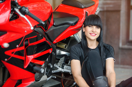 A biker girl in black clothes on a sports motorcycle posing while sitting in the city. Banco de Imagens