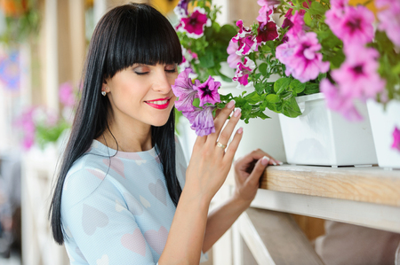 girl in a blue dress, fashionable with black hair walking in the city, terrace with flowers.