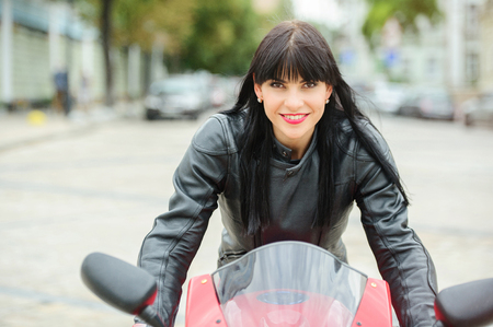 A biker girl in a leather jacket on a motorcycle posing in the city.