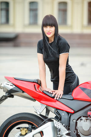 Girl biker in black clothes on a sports motorcycle posing in the city. Stock Photo
