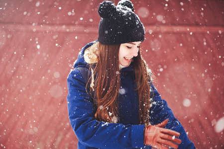 Winter portrait of a young woman. Beauty Joyous Model A girl laughs and is happy to have a dark red background. Beautiful young woman outdoors. Enjoy nature, in winter.