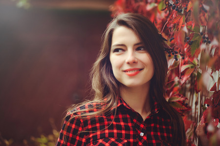 Smiling young brunette woman posing in the courtyard of her residence in a red checkered shirt is happy, portrait happy carefree, health in cushy tones. Stock Photo