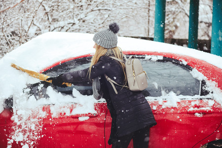 Winter portrait of a young woman cleaning snow from a car. Beauty blonde Model Girl laughs and cheerfully cleans the snow. Beautiful young woman outdoors.
