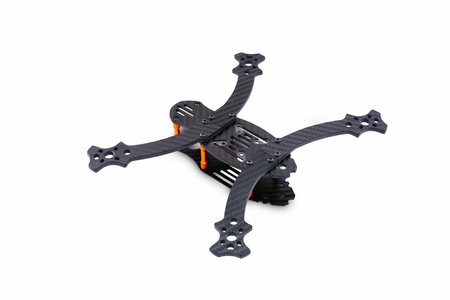 The beginning of the racing drone assembly. A robust frame of an unmanned aerial vehicle made of carbon fiber. Frame of carbon fiber quadrocopter isolated on white background.