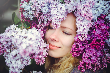 Outdoor fashion photo of a beautiful young blue-eyed woman. Spring color. beautiful blonde girl in lilac flowers. Perfume with a scent of flowers. Perfumes and beauty.