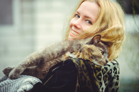 beautiful blond woman with big cat outdoors holds on shoulder and smiles.