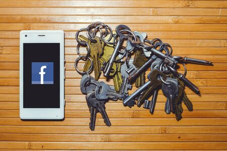 Kiev, UKRAINE - APRIL 2018: threat of blocking and banning facebook, encryption keys are located next to the phone