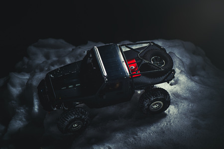 Radio-controlled car in the snow at night, lights shine. Christmas entertainment gift rc car.