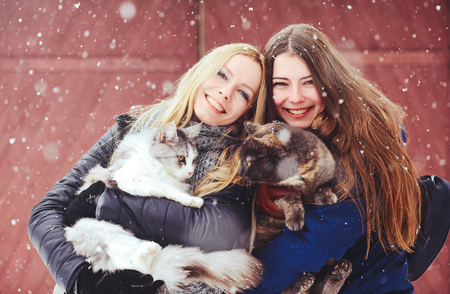 two beautiful girls with big cats in the winter outside, animal protection, fun in nature.