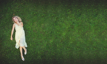Beautiful young woman lying on the grass. Fresh natural summer concept. View from above. - image