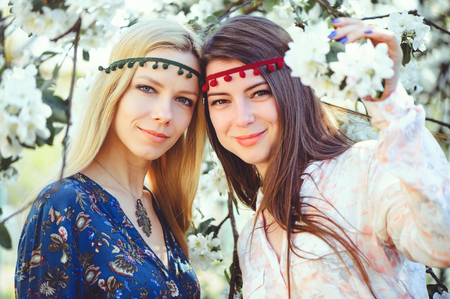 Portrait of young beautiful women smiling in the flowered garden in the spring time. Almond flowers are blooming. The girl is dressed stylishly, jewelry on her head. - image