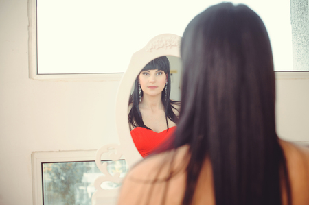 Girl trying to dress looking in the mirror, cheerful and happy. Cute beautiful mixed race Asian / Caucasian young woman in red dress. - Image