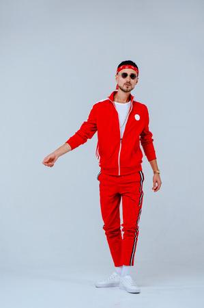 salud, diversión, gente concepto de deporte - joven feliz con traje deportivo rojo sobre fondo blanco.