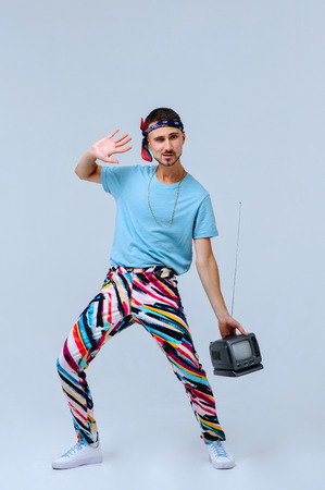fashionable man in bright pants, with a small TV, the manifestation of emotions, the imposition of opinions, gestures with hands a place for the text. Imagens