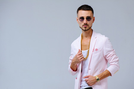 fashionable sophisticated man in a pink jacket and black trousers, wears a gold chain, the expression of emotions gestures with his hands. Standard-Bild