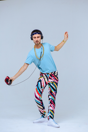 fashionable bright man in headphones in retro style manifestation of emotions of joy, gestures with hands space for text.
