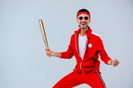 alegre hombre de moda con un traje deportivo rojo en la mano un bate de béisbol de oro está más que un poco sorprendido. orgulloso y exitoso.