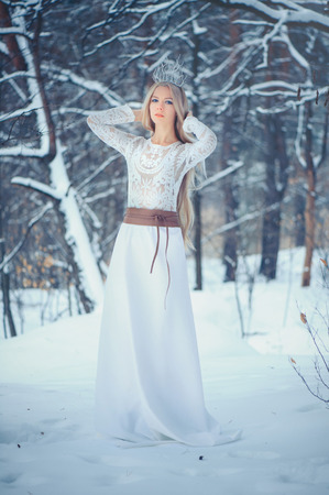 Winter Beauty Woman. Beautiful fashion model girl with snow hairstyle and makeup in the winter forest.