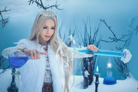 Winter Beauty Woman. Beautiful fashion model girl with glass flasks hairstyle and make-up in winter laboratory. Imagens
